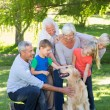 Happy family petting their dog — Stock Photo #69008835