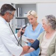 Doctor checking patients blood pressure — Stock Photo #69009883