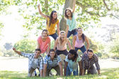 Happy friends in the park making human pyramid — Stock Photo