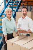 Smiling warehouse managers with clipboard — Stock Photo