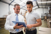 Warehouse manager using tablet pc with colleague — Stock Photo