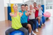 People gesturing thumbs up in health club — Stock Photo