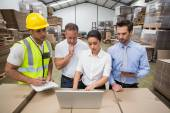 Warehouse managers and worker looking at laptop — Stock Photo