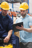 Focused warehouse workers talking together — Stock Photo