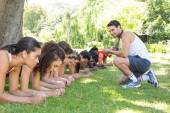 Fitness group planking in park with coach — Stock Photo