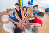 Fit people stacking hands at health club — Stock Photo