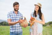 Happy farmers holding chicken and eggs — Stockfoto