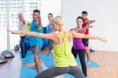People practicing warrior pose in fitness club — Foto de Stock