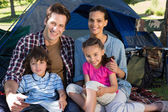Happy family on a camping trip in their tent — Stock Photo