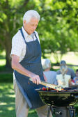 Concentrate grandfather doing barbecue — Stock Photo