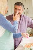 Woman putting flour on husbands nose — Stock Photo