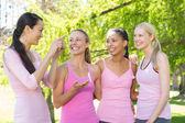 Smiling women in pink for breast cancer awareness — Stock Photo