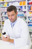 Handsome pharmacist lokking at medicines bottle — Stock Photo