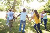 Amici felici nel parco che tengono le mani — Foto Stock