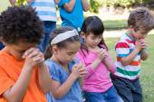 Children saying their prayers in park — Stock Photo