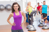 Happy fit woman standing hands on hips at gym — Stock Photo