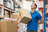 Worker with backache while lifting box in warehouse — Stock Photo