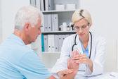 Physiotherapist examining patients wrist — Stock Photo