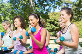 Fitness group lifting hand weights in park — Stock Photo