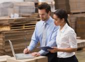 Warehouse managers working on laptop — Stock Photo