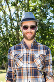 Handsome hipster smiling in the park — Stockfoto