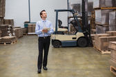 Manager holding clipboard in warehouse — ストック写真