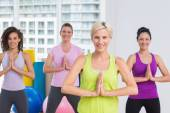 Women with hands joined exercising at gym — Stock Photo