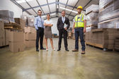 Warehouse team standing looking at camera — Stock Photo