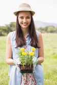 Happy woman holding potted flowers — Stock Photo