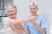 Nurse assisting patient in raising arm — Stock Photo