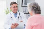 Doctor writing prescriptions for patient — Stock Photo