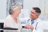 Male doctor looking at female patient — Stock Photo