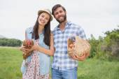 Happy farmers holding chicken and eggs — Stock Photo
