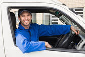 Delivery driver smiling at camera in his van — Stock Photo