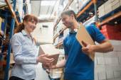Delivery man passing parcel to warehouse manager — Stock Photo