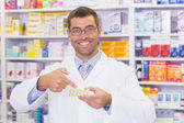 Pharmacist pointing blister packs — Stock Photo