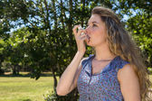 Pretty blonde using her inhaler — Stock Photo