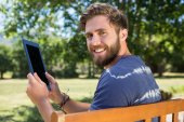 Man using tablet on park bench — Stock Photo