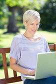 Smiling blonde using laptop in park — Stockfoto
