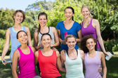 Fitness group smiling at camera in park — Stock Photo
