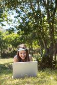 Pretty brunette using laptop in park — Stock Photo