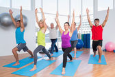 People exercising with hands raised at fitness club — Stock Photo