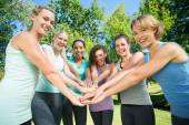 Fitness group putting hands together — Stock Photo