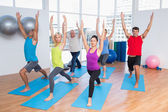 People with hands raised doing yoga — Stock Photo