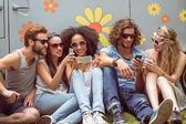 Hipster friends using their phones — Stock Photo