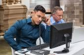 Warehouse managers using telephone and laptop — Stock Photo