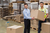 Warehouse worker and manager carrying box — Fotografia Stock