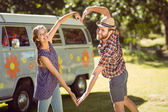 Hipster couple making heart with arms — Stock Photo