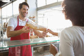 Baker doing loaf transaction with customer — Stock Photo
