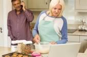 Blonde preparing dough with husband behind — Stock Photo